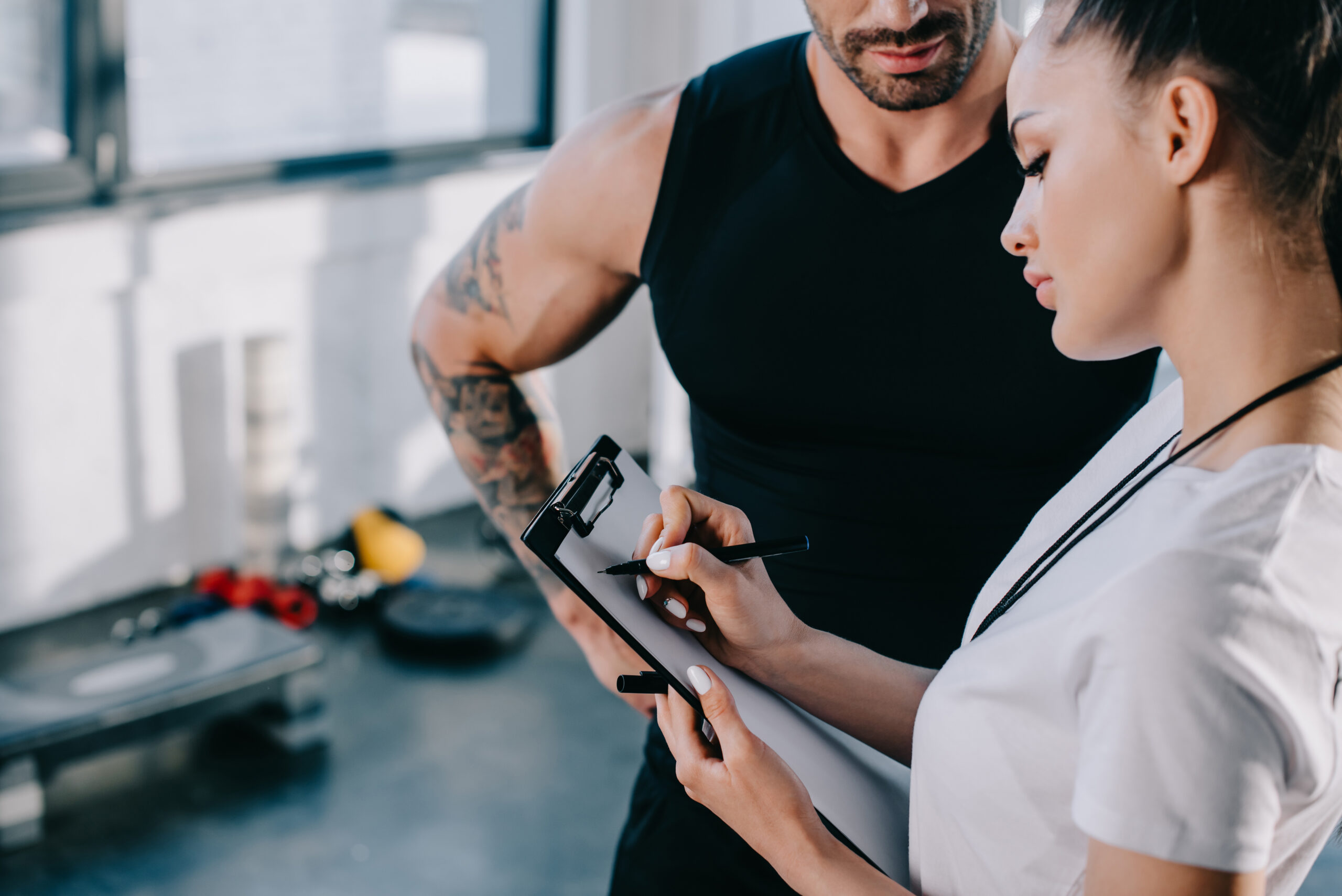 female personal trainer writing on clipboard and sportsman standing near at gym