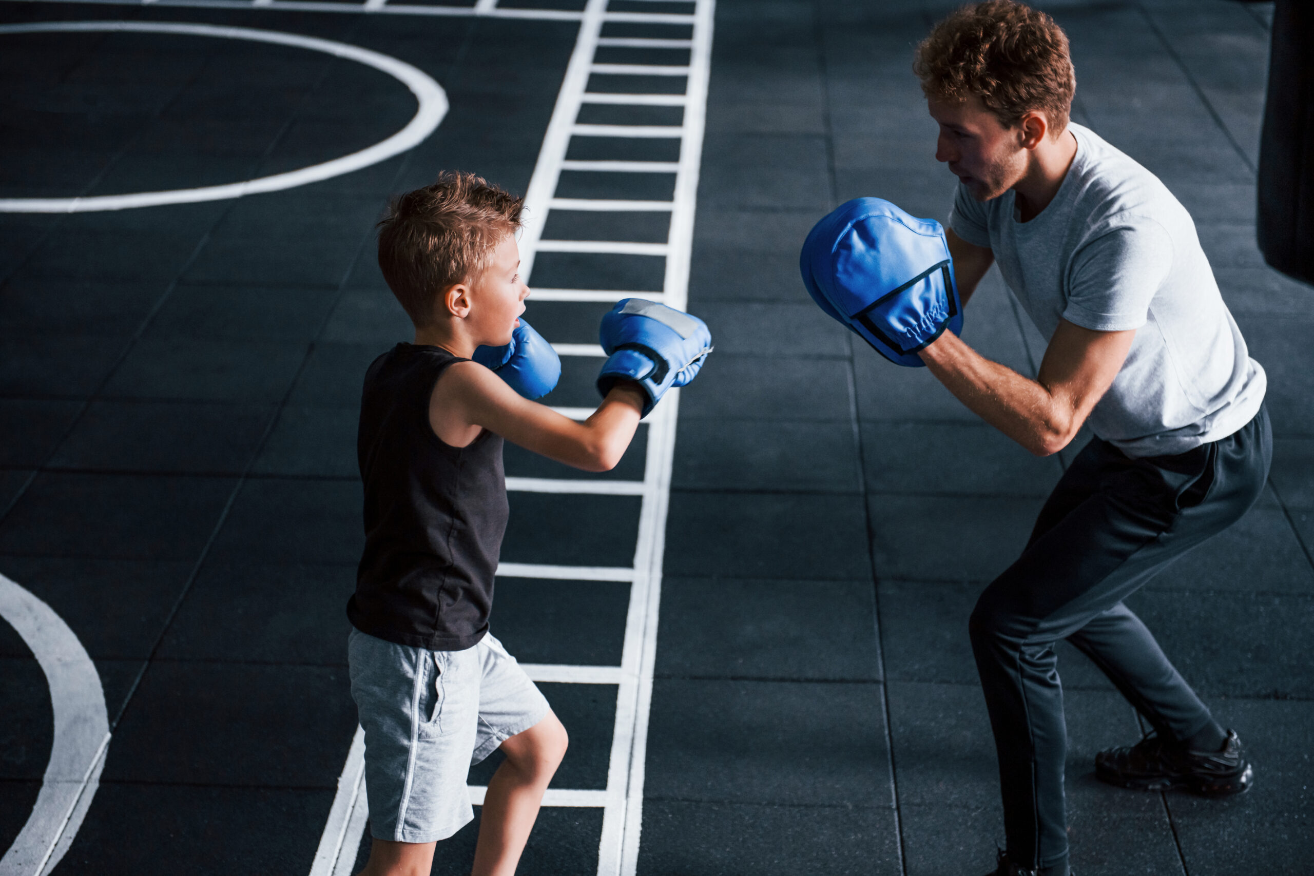Young trainer teaches kid boxing sport in the gym
