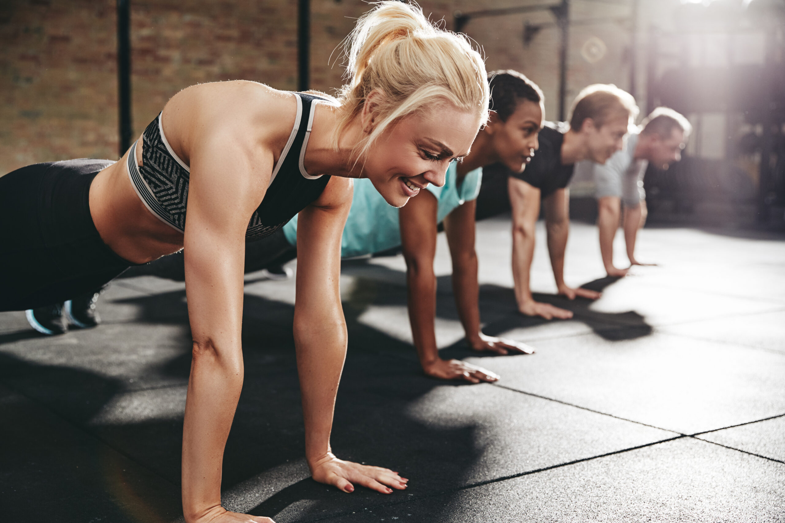 Smiling woman doing pushups during an exercise class